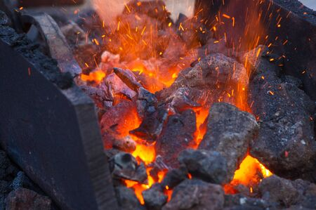 blacksmith furnace with burning coals, tools, and glowing hot metal workpieces, close-up Archivio Fotografico