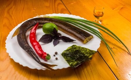 still life - smoked garfish with lime, Basil, green onions, chili, nori chips, spices, olive oil in a white ceramic dish, on a wooden table Imagens - 133181386