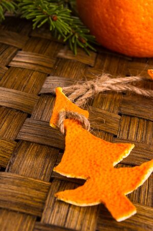 New Year Concept. Christmas decorations from tangerine peel, fir-tree branches and the fruits of mandarin orange on woven mat background