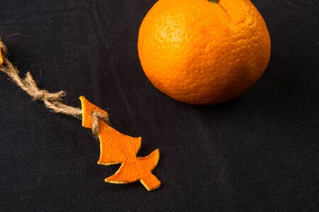 New Year Concept. Christmas decorations from tangerine peel and the fruits of mandarin orange on black background Imagens