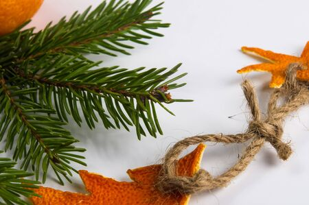 New Year Concept. Christmas decorations from tangerine peel, fir-tree branches and the fruits of mandarin orange on white background Imagens - 133178735