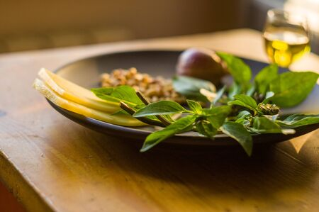 Fresh ingredients for preparing Italian pesto sauce - lemon basil sprigs, peeled seeds of cedar nuts, large garlic clove, Greek olive oil, Parmesan cheese, on a ceramic plate, in scattered sunlight Imagens - 133181073