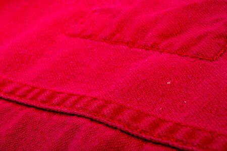 clothing items washed red cotton fabric texture with seams, clasps, buttons and rivets, macro, close-up