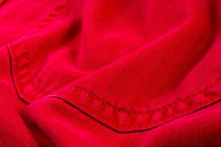 clothing items washed red cotton fabric texture with seams, clasps, buttons and rivets, macro, close-up Imagens