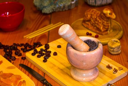 preparation of treats for traditional Orthodox Christmas - handmade baked cookies in the form of lambkin, dried fruits, cranberries, honey, nuts, rice pudding, mortar with poppy seeds, Church candles on a wooden table