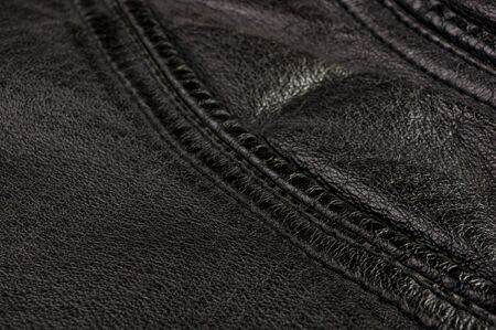 Old vintage genuine soft black leather texture background, top layer with pores and scratches, macro Imagens