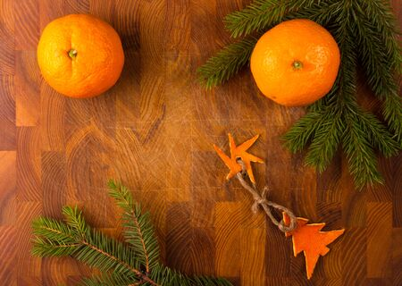 New Year Concept. Christmas decorations from tangerine peel and fir-tree branches and the fruits of mandarin orange on wooden background Imagens