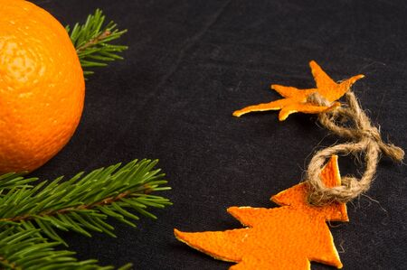 New Year Concept. Christmas decorations from tangerine peel, fir-tree branches and the fruits of mandarin orange on black background Imagens