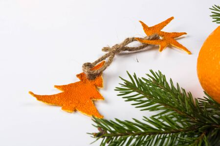 New Year Concept. Christmas decorations from tangerine peel, fir-tree branches and the fruits of mandarin orange on white background Imagens