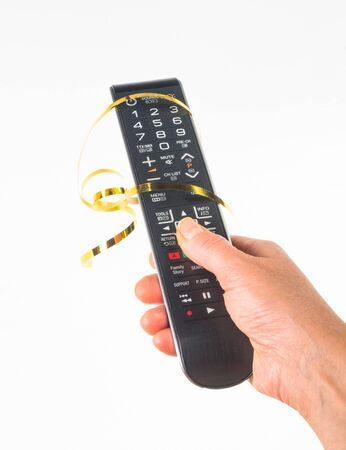 hand holding a remote control in a festive gold ribbon on white background