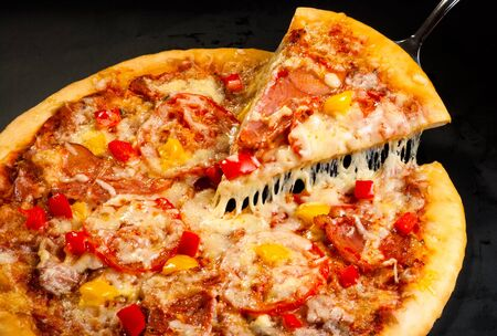 pizza on a dark background with ham, mushrooms, cheese and sweet pepper