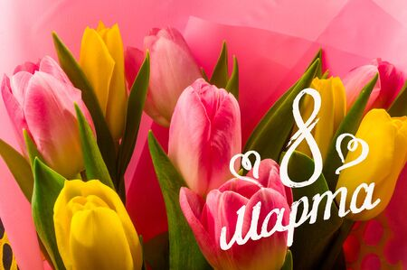Greeting card - a bouquet of fresh spring pink and yellow tulips, holiday greetings, handwritten inscription with a brush 8 march, greeting lettering, russian text. 版權商用圖片