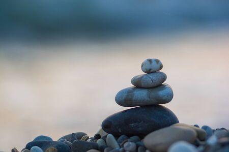 Pierres de galets zen pyramide pliée sur la plage de la mer au coucher du soleil