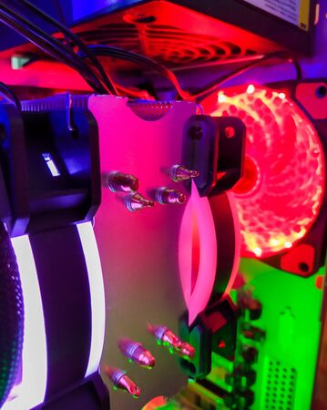 Modern computer air cooling with multi-colored led backlight-fans, cooling radiators, cables, boards, close-up.