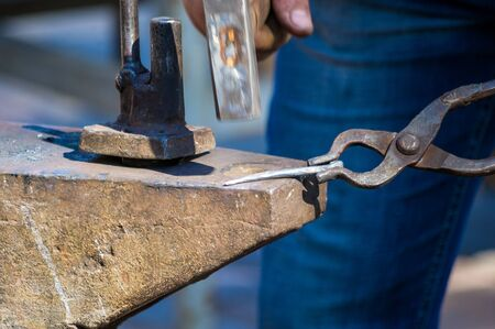 blacksmith performs the forging of hot glowing metal on the anvil, close-up Standard-Bild