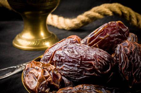 Big luxury dried date fruit in bowls on the dark surface, kurma ramadan kareem concept. Stock Photo