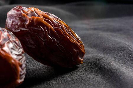 Big luxury dried date fruit on the dark surface, kurma ramadan kareem concept.