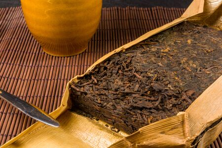 Chinese pressed PU-erh tea in bamboo leaf packaging and tea knife on a bamboo Mat, close-up