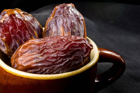 Big luxury dried date fruit in bowls on the dark surface, kurma ramadan kareem concept. Stock Photo