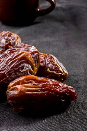 Big luxury dried date fruit on the dark surface, kurma ramadan kareem concept.
