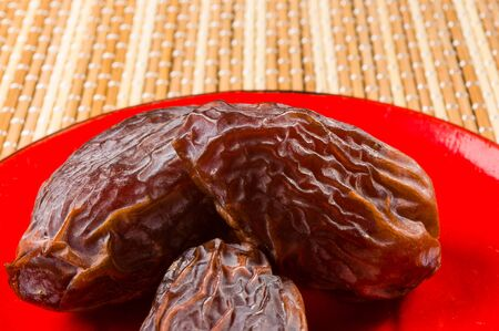 Big luxury dried date fruit in bowls on the bamboo mat, kurma ramadan kareem concept.