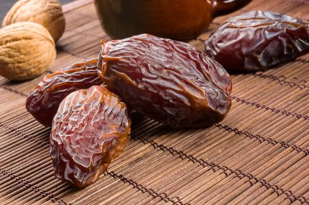 Big luxury dried date fruit on the bamboo mat, kurma ramadan kareem concept.