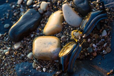 eyeglasses for swimming on a pebble beach in the sea waves, a warm summer day, close-up