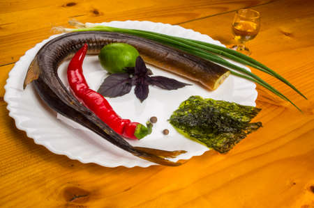 still life - smoked garfish with lime, Basil, green onions, chili, nori chips, spices, olive oil in a white ceramic dish, on a wooden table