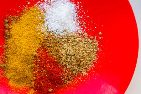Spices - red paprika, ground coriander, salt and turmeric on a red plate, close up