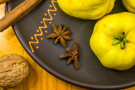 still life - large yellow quince fruits on a ceramic plate, with anise, cinnamon, and walnuts