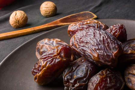 Big luxury dried date fruit in bowls on the dark surface, kurma ramadan kareem concept. Banco de Imagens