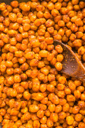 Cooking chickpeas with spices in a pan, close up