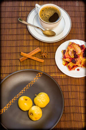 Still life - a cup of black coffee, homemade cookies with fruit, baked apples on a bamboo mat