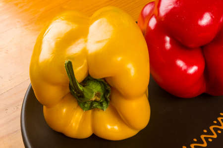 a colorful mix of the freshest red and yellow paprika, bell pepper in ceramic plate on wooden background, close up