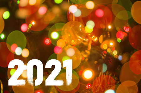 Christmas background-garlands with colorful lights on a decorated Christmas tree, bokeh, Happy New Year 2021 colored symbol and text in trendy flatten style design.