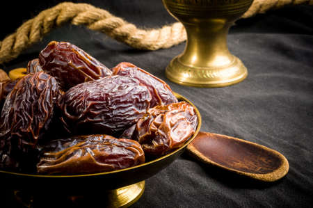 Big luxury dried date fruit in bowls on the dark surface, kurma ramadan kareem concept. Imagens