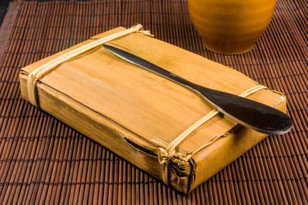 Chinese pressed PU-erh tea in bamboo leaf packaging and tea knife, close-up