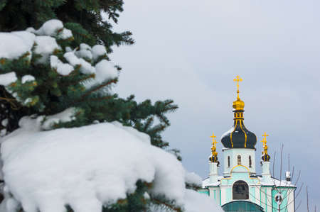 Winter landscape - Orthodox church in the snow among fir-trees on a frosty day
