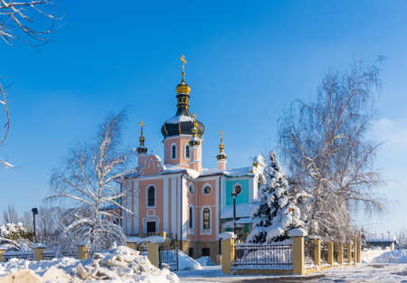 Winter landscape - Orthodox church in the snow among trees on a frosty day Stock Photo