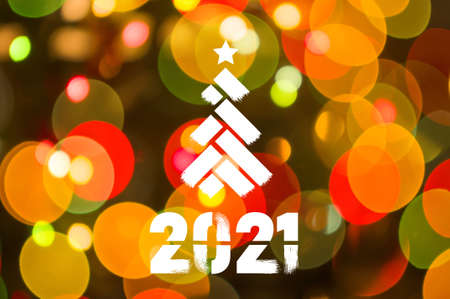 Christmas background-garlands with colorful lights on a decorated Christmas tree, bokeh, Happy New Year 2021 colored symbol and text in trendy flatten style design for seasonal holidays flyers, greetings and invitations cards and christmas themed congratulations and banners