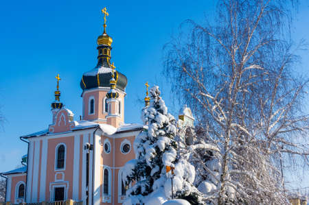Winter landscape - Orthodox church in the snow among trees on a frosty day Imagens