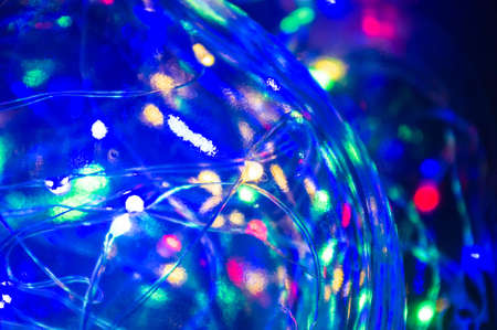 Glowing Christmas multicolored LED garland in a glass bottle, black background, macro, close-up