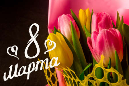 Greeting card - a bouquet of fresh spring pink and yellow tulips, holiday greetings, handwritten inscription with a brush 8 march, greeting lettering, russian text. Text translation - 8 march. Stock Photo