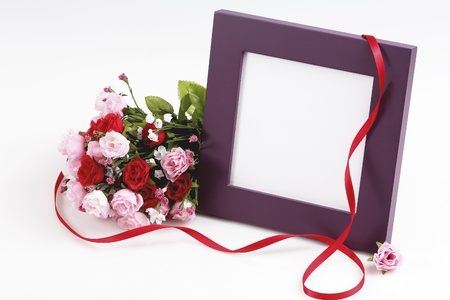 Nicely displayed blank picture frame wih fake bouquet of roses and red ribbon photo