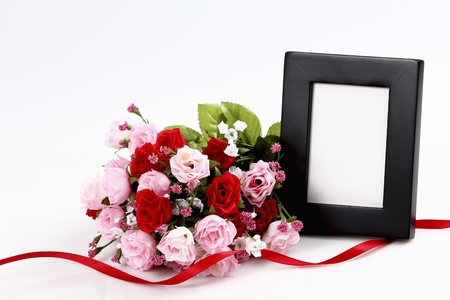 Blank picture frame with bouquet of roses photo