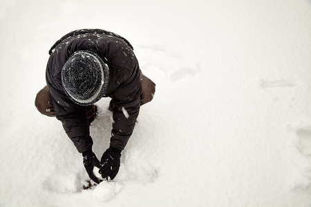 snow ball: young adult in snow storm making snow ball Stock Photo