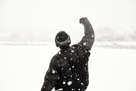 icey: young adult in snowstorm with fist raised