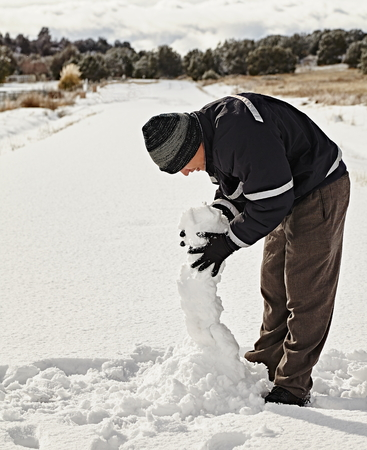 icey: young adult in snow storm making snowman and smiling