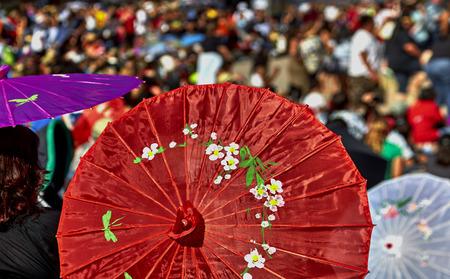 sun umbrellas: Crowd of people watching the Aloha Festival Show under sun Umbrellas