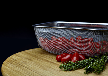 sprigs: Stainless steel basket filled with plum tomatoes with rosemary sprigs on a bamboo cutting board isolated on black